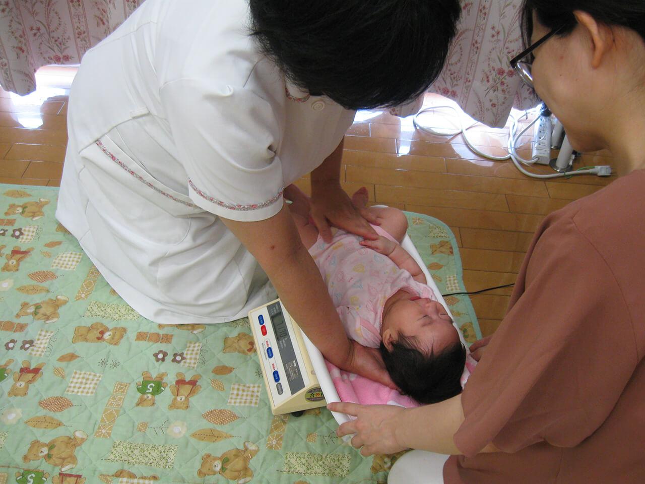 赤ちゃんの体重を測る助産師